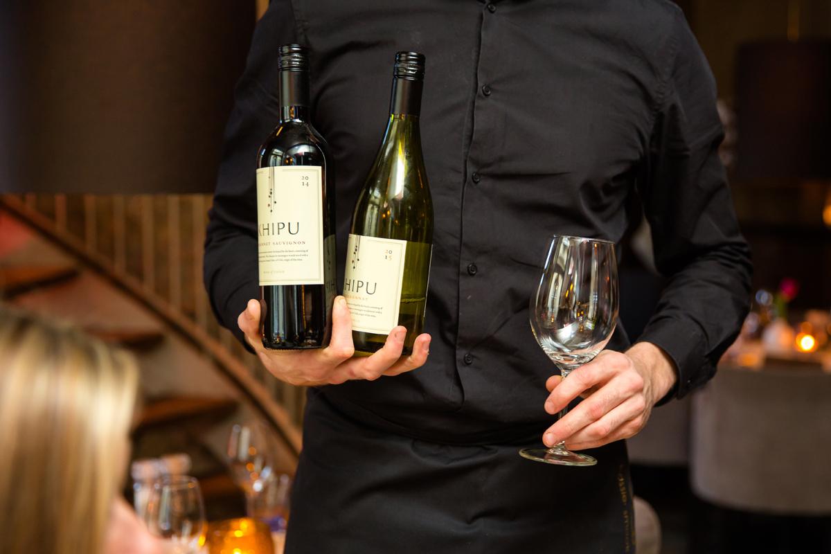 Ober met verschillende wijnen in de handen